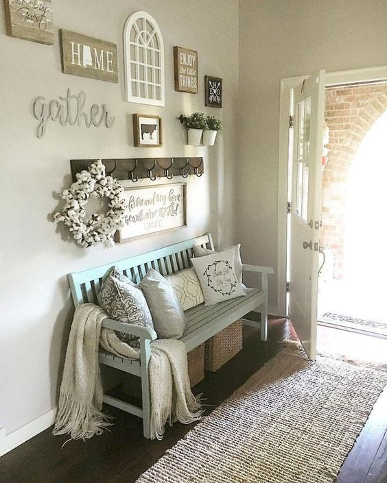a light blue bench, some woven boxes for storage, pillows and a gallery wall for a cozy rustic feeling