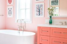 a light pink bathroom with a gallery wall, a coral vanity, a coral printed rug for a unique and very cute look