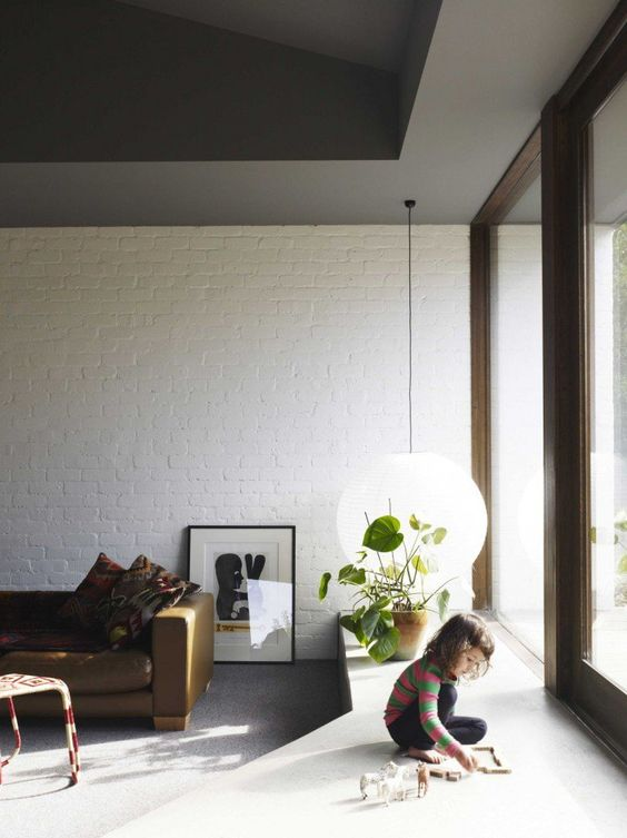 a mid-century modern meets minimalist living room with white brick walls and a glazed wall to bring more natural light to the space