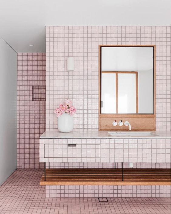 a millenial pink bathroom with a floating vanity clad with tiles, stained wood and black grout to make a contrast