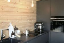 a minimalist black kitchen with a wooden wall-backsplash and pendant bulbs is very stylish and edgy