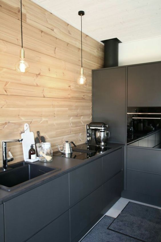 a minimalist black kitchen with a wooden wall backsplash and pendant bulbs is very stylish and edgy