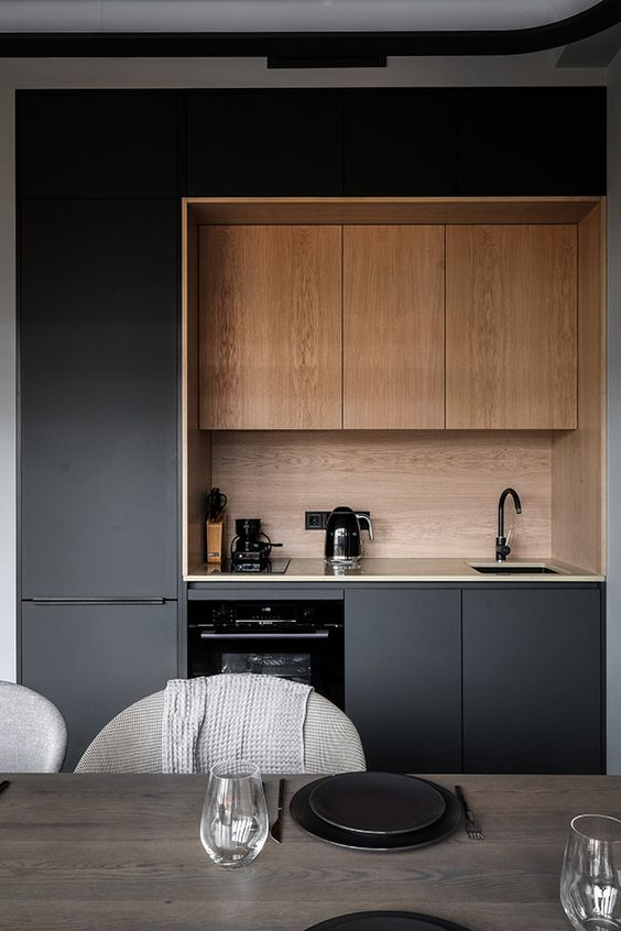 a minimalist black kitchen with sleek cabinets, a wooden backsplash and upper cabinets plus black fixtures for more chic