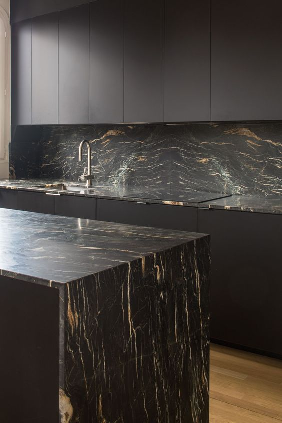 a minimalist black kitchen with sleek cabinets, black marble countertops and a backsplash and neutral fixtures