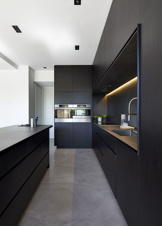 a minimalist black kitchen with sleek cabinets, built-in lights, a large kitchen island and built-in appliances