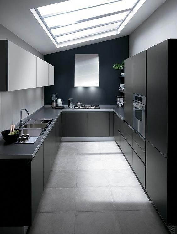 a minimalist black kitchen with sleek cabinets, grey stone countertops, white upper cabinets and a large skylight