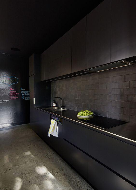 a minimalist black kitchen with sleek metal cabinets, a brick backsplash and a chalkboard wall looks wow