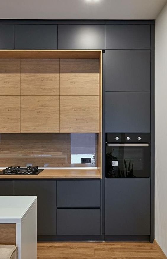 a minimalist graphite grey kitchen with sleek cabinets, a wooden backsplash and built in upper cabinets is very chic