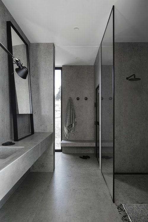 a minimalist grey bathroom done in concrete, with black fixtures and touches, with a large mirror and a window