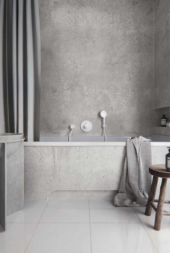 a minimalist grey bathroom done with concrete and tiles, with a niche for storage, a large curtain, a concrete vanity and a wooden stool