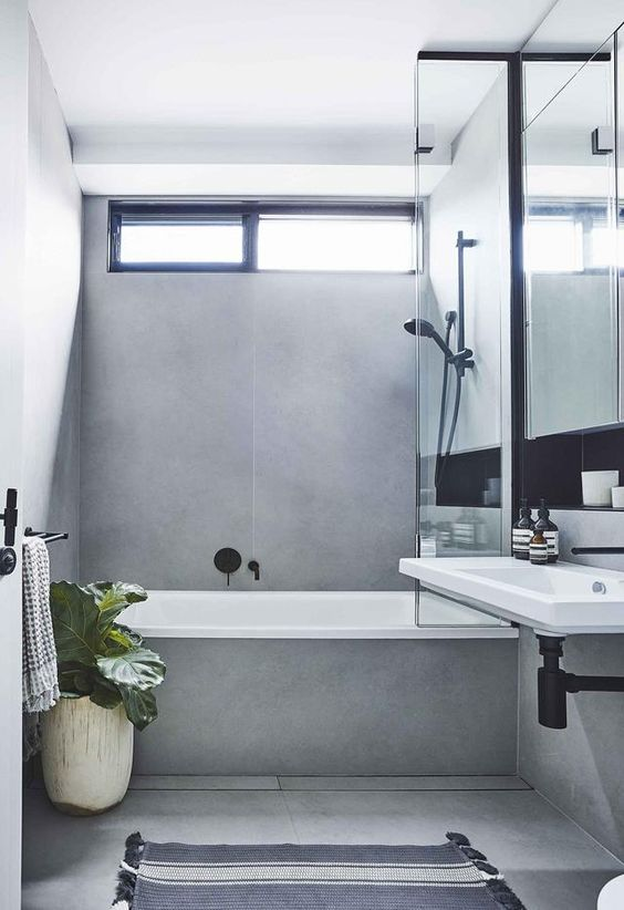 a minimalist grey bathroom done with large scale tiles, with black fixtures and potted plants plus a wall-mounted sink