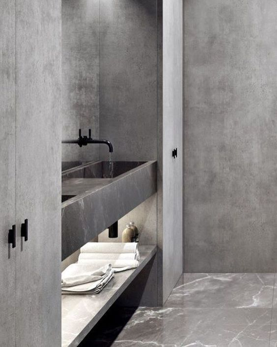a minimalist grey bathroom done with marble, stone and concrete, with black fixtures and plenty of storage space