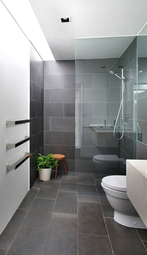 a minimalist grye bathroom clad with tiles, with a glass enclosed shower, white appliances and potted greenery