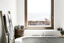a minimalist industrial bathroom with a concrete floor and bathtub, touches of wood and wicker, textiles and a large window for views