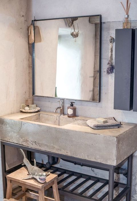 a minimalist industrial bathroom with concrete walls, a concrete and metal vanity, pendant lamps and a large mirror