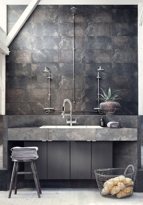 a minimalist industrial bathroom with dark stone tiles, a stone vanity, neutral fixtures and wooden furniture
