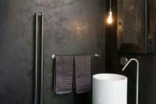 a minimalist industrial bathroom with darkened metal walls, a free-standing sink, exposed piping and pendant bulbs