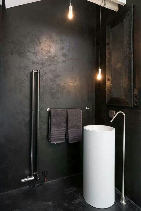 a minimalist industrial bathroom with darkened metal walls, a free standing sink, exposed piping and pendant bulbs