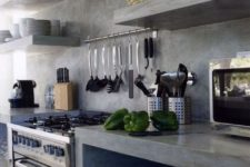 a minimalist industrial kitchen with concrete walls, cabinets, shelves and hood, metal appliances and some tableware