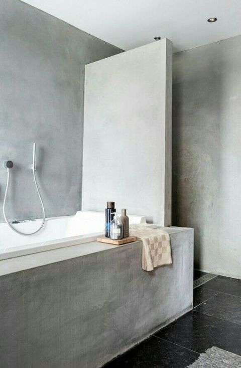 a minimalist industrial space with concrete walls, a dark tile floor, a concrete tub and neutral fixtures