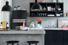 a minimalist industrial space with concrete walls and a kitchen island, black metal cabinets and lamps plus metal stools