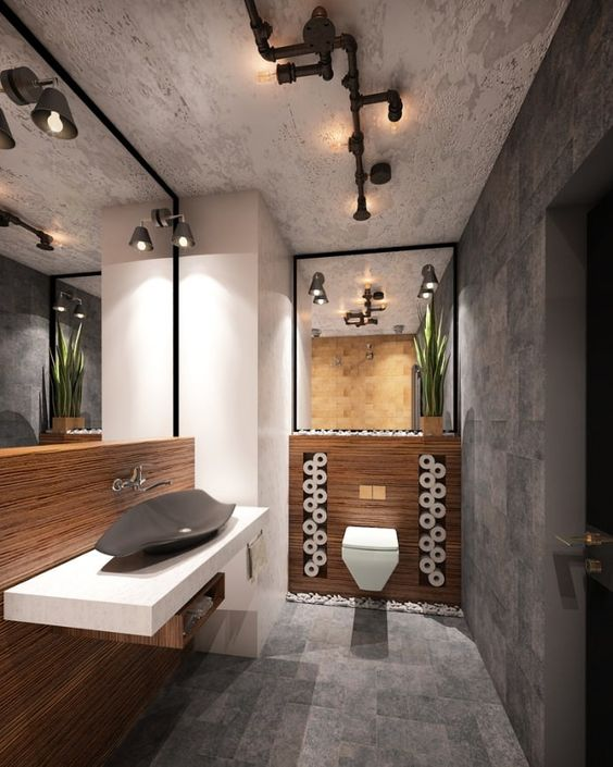 a minimalist industrial space with stone tiles, wooden accents, large mirrors and exposed pipes that are lamps