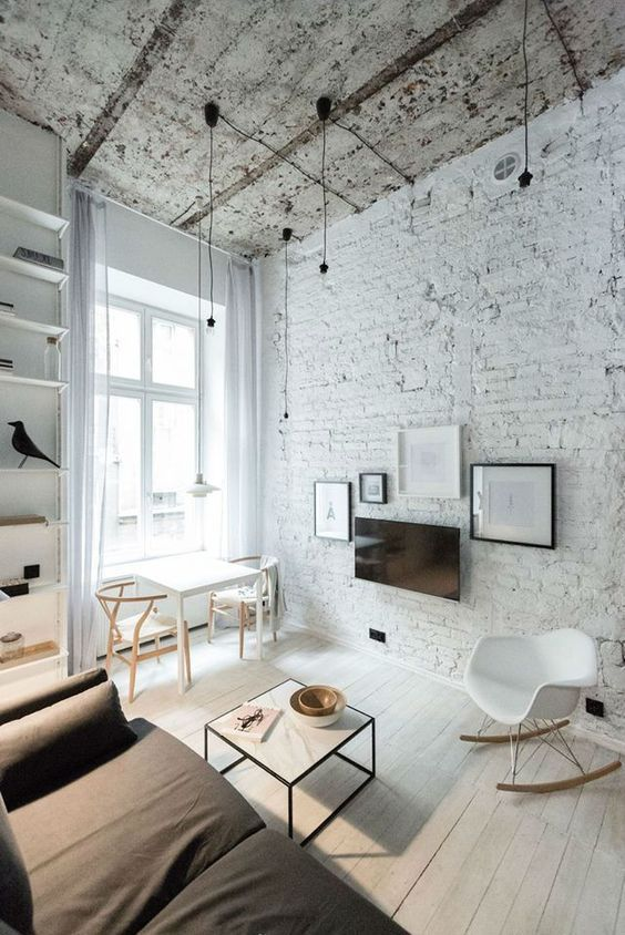 a minimalist living room with a white brick wall and a shabby ceiling to make this space more eye-catching and give it a character