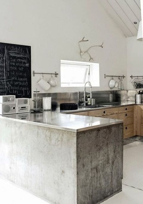 a minimalist meets industrial kitchen with concrete cabinets and stone countertops, a metal backsplash and a chalkboard