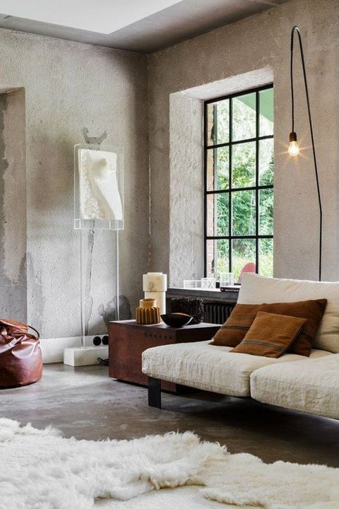 a minimalist meets industrial living room with concrete walls, a vintage chest, a cozy sofa, a faux fur rug, bulbs looks wow