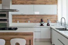a minimalist white kitchen with sleek cabinets, a wooden wall and backsplash plus a kitchen island to echo it