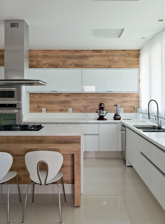 a minimalist white kitchen with sleek cabinets, a wooden wall and backsplash plus a kitchen island to echo it