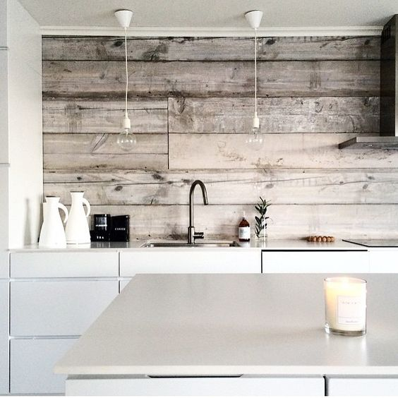 a minimalist white kitchen with sleek cabinets and a kitchen island and whitewashed wooden backsplash looks cozy and ethereal