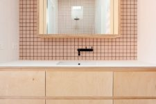a modern bathroom clad with pink tiles and black grout, with light-colored MDF furniture and black fixtures