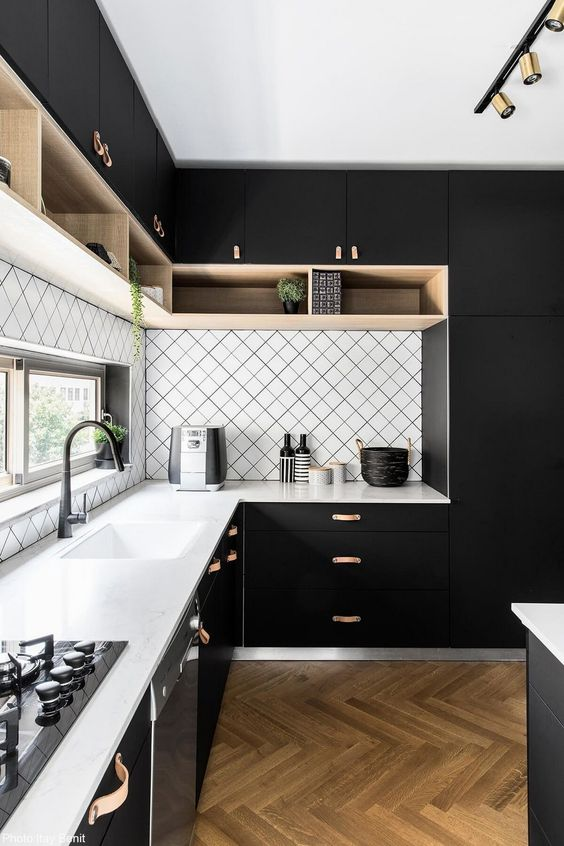 a modern black kitchen with a geometric backsplash and white countertops plus touches of wood