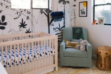 a modern boho jungle nursery with a statement black and white wall, layered rugs, animal toys and bright furniture