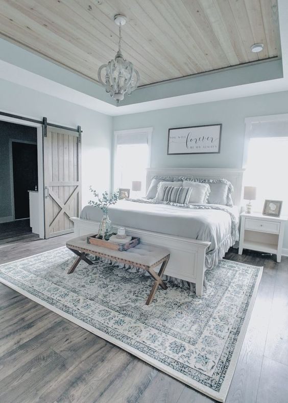 a modern farmhouse bedroom with white furniture, an upholstered bench, a vintage chandelier and ruffle bedding