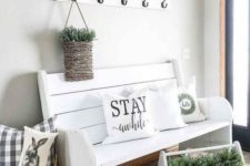a modern farmhouse entryway with white furniture, a basket with pillows, a tool box and a basket with greenery
