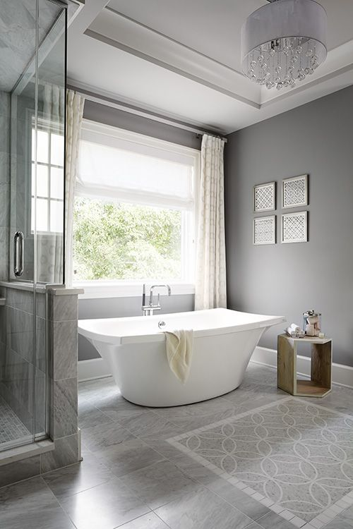 a modern grey bathroom done with tiles on the floor, a catchy free-standing tub, a wooden table and a crystal chandelier