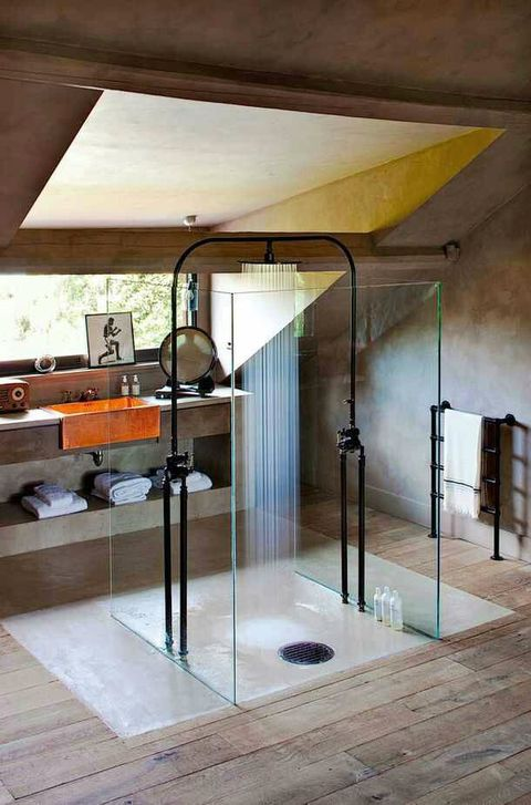 a modern industrial bathroom all done with wood, with black shower fixtures, a concrete and wood vanity