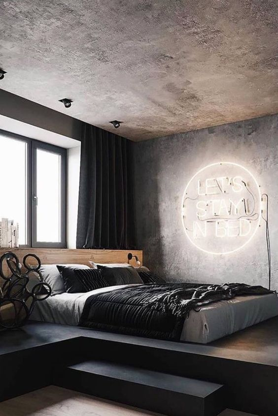 a modern industrial bedroom with a concrete ceiling and walls, a neon light, a platformbed and dark textiles