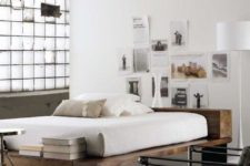 a modern industrial bedroom with a grid wall, a rough wood bed, a metal chair and faux animal skins and a metal chair