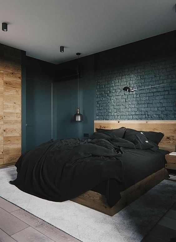 a modern industrial farmhouse bedroom with black brick walls, a neutrla wooden bed and wall and dark lamps