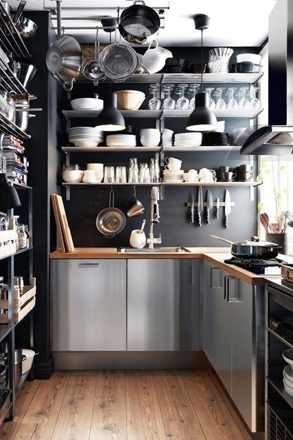 a modern industrial kitchen with black walls, metal cabinets, open shelves and wooden countertops is chic