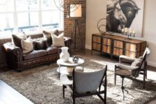 a modern industrial living room with a faux brick wall, modern furniture, a wood and metal dresser and a chic sphere chandelier