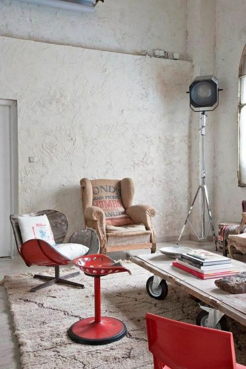 a modern industrial living room with plaster walls, red furniture, a wood and metal table, metal lamps and a rug