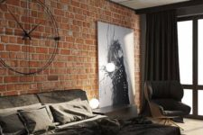 a modern industrial space ith brick walls, a concrete ceiling, an upholstered bed, a statement artwork and unique industrial clock