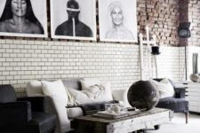 a modern meets industrial living room with brick walls, vintage and industrial furniture, a gallery wall and metal lamps