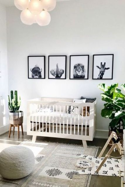 a modern tropical nursery with potted plants, bubble chandelier, black and white artworks and layered rugs