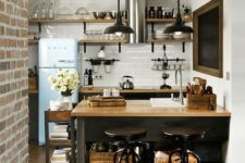 a monochromatic kitchen with light wooden countertops, black lamps and stools and crates for storage