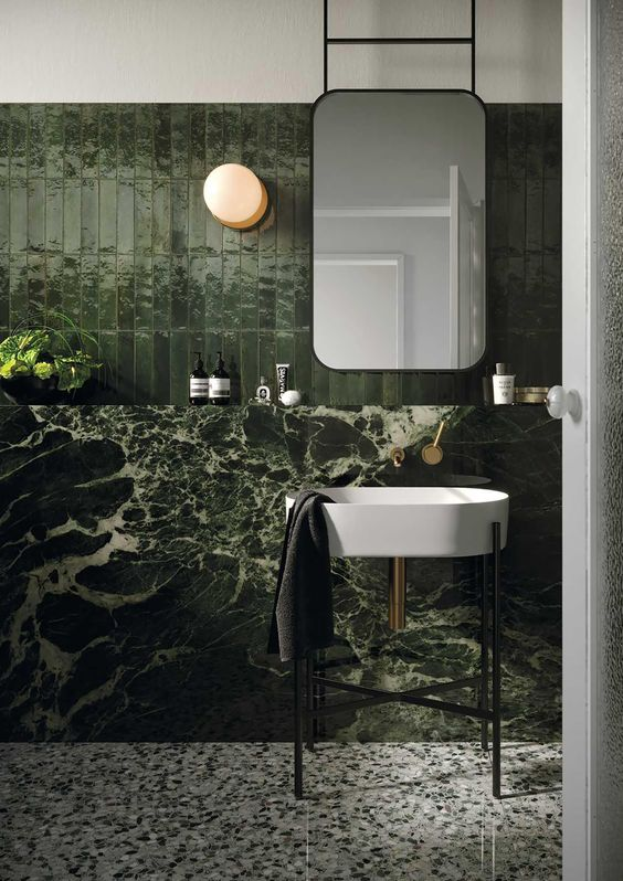 a moody green bathroom clad with tiles and marble, with tile floors, catchy appliances and a mirror on the wall